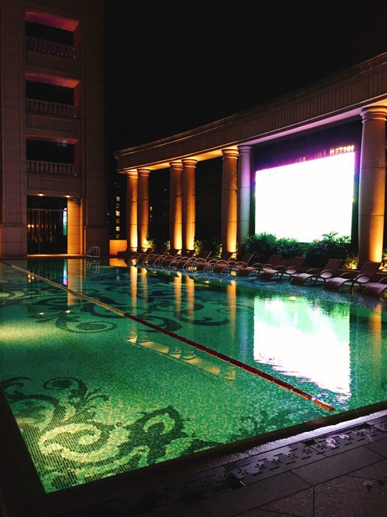 飯店游泳池一隅,有大螢幕看轉播